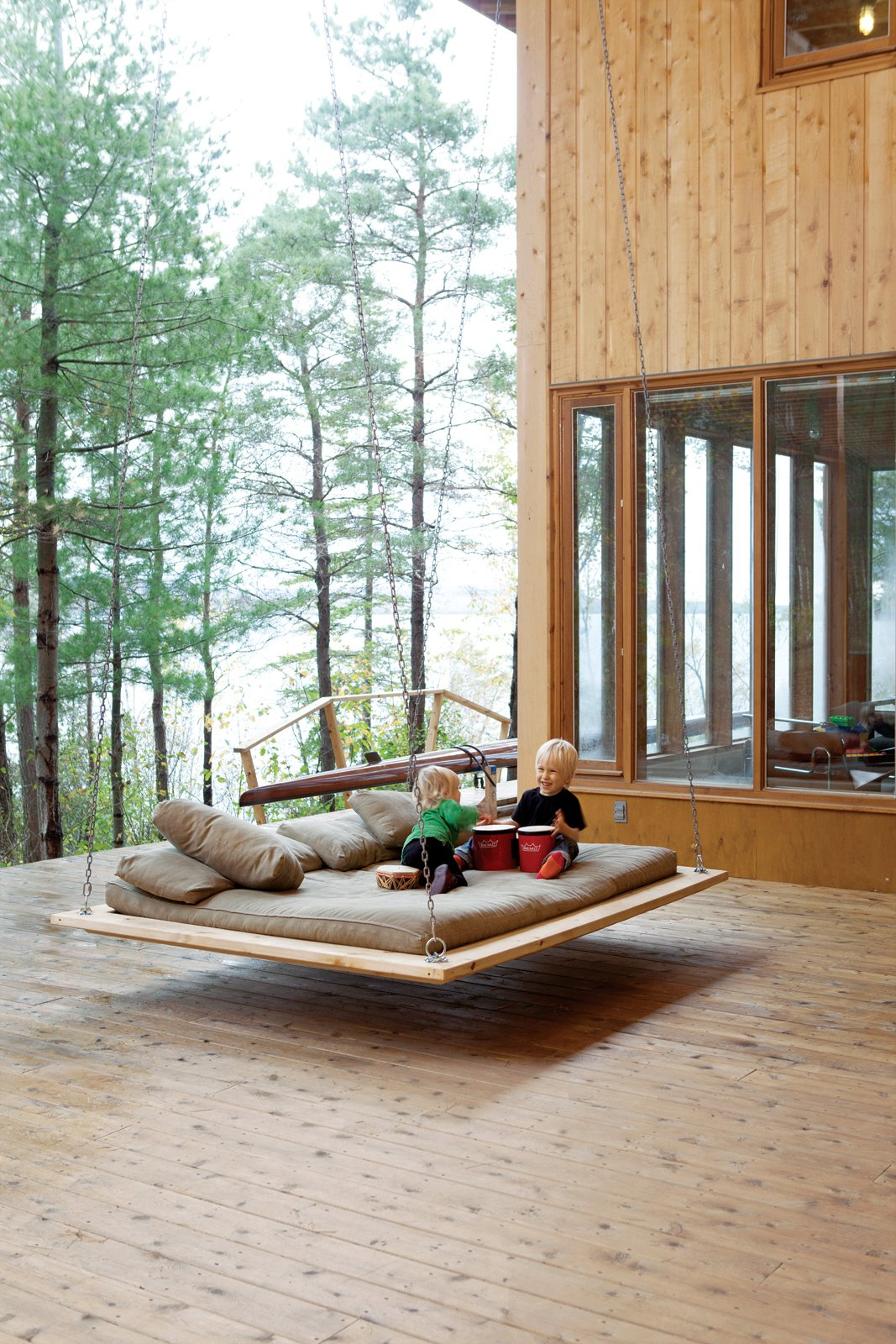 "Two-year-old Annika and five-year-old Soren make music on the ""nap swing,"" a popular hangout spot for kids and adults alike. Tagged: Outdoor, Large Patio, Porch, Deck, and Wood Patio, Porch, Deck.  Outdoor by Joe Pirrello from Four Friends Joined Forces to Realize This Idyllic Forest Retreat Outside Toronto"