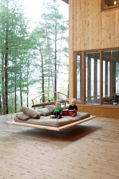 """Two-year-old Annika and five-year-old Soren make music on the """"nap swing,"""" a popular hangout spot for kids and adults alike."""