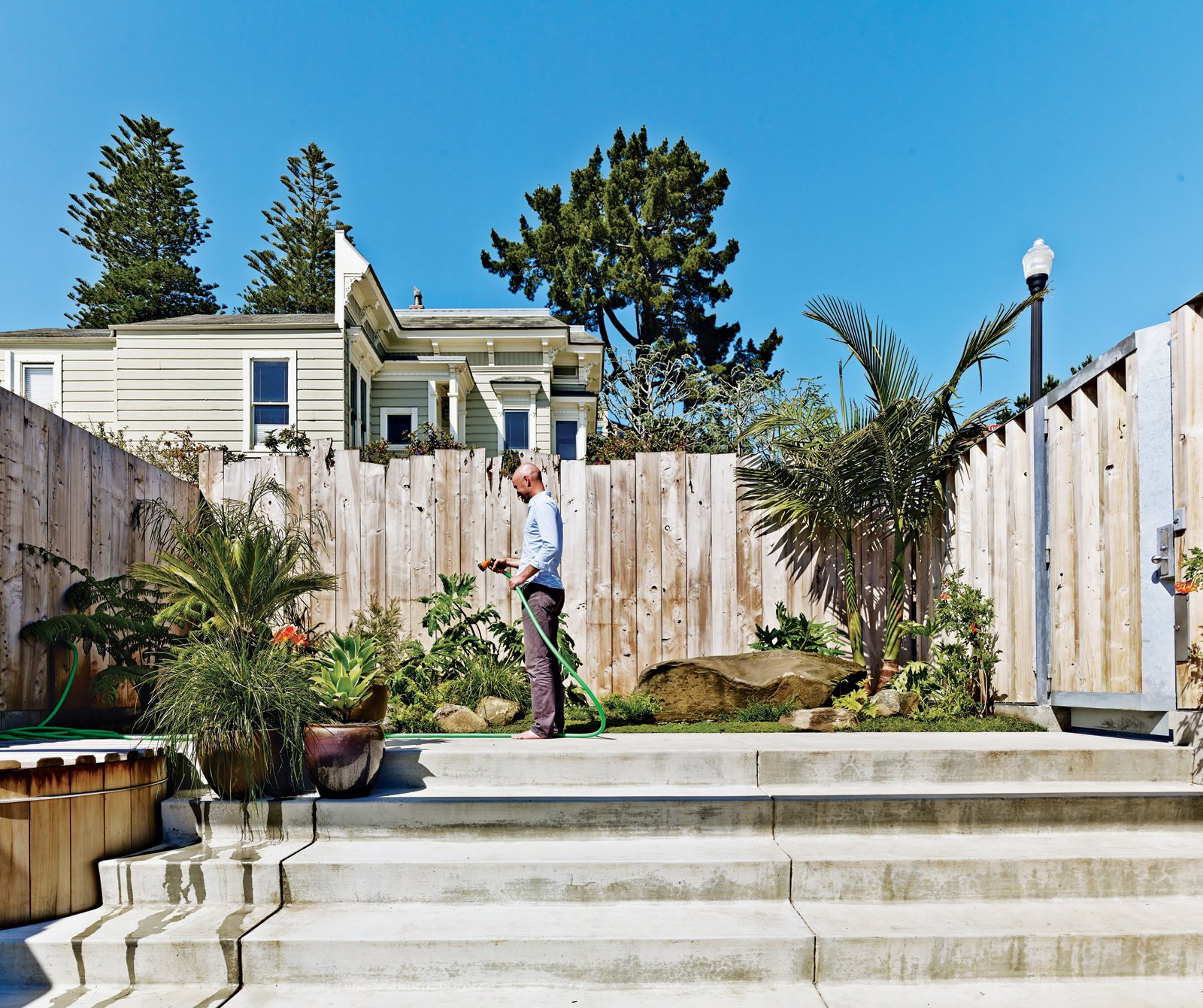 Russell-Clarke tends a small garden.  Photo 4 of 17 in Striking Slatted Wood and Glass Home in San Francisco