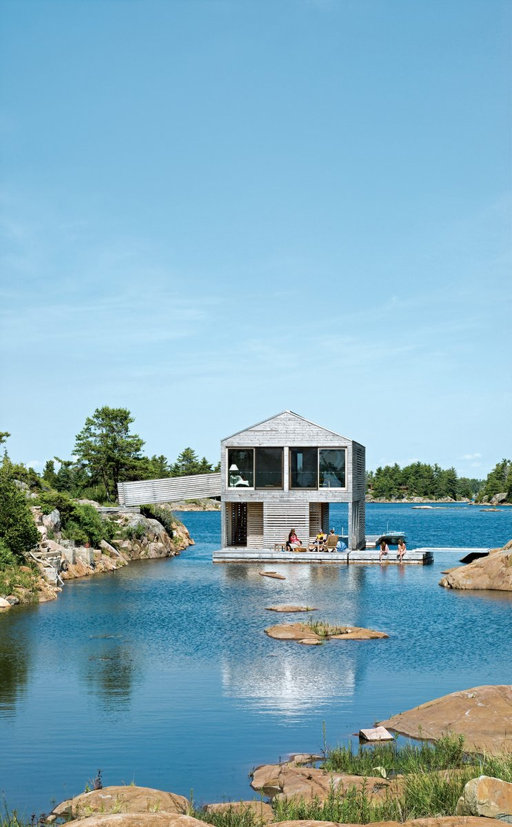 """Cedar slats mark the facade of Floating House, Doug and Becca Worple's lake house in Ontario. The architects, MOS, chose materials and shapes that wouldn't stand out. """"They're really simple, almost Platonic forms,"""" principal Michael Meredith says. The modest cabin has boat, a gabled roof and a cladding of untreated cedar, a material that shows up on docks and homes along Georgian Bay. """"Allowing the buildings to weather seems the right thing to do,"""" Sample says. And it's ready for winter: Sliding barn doors seal the place up as an impenetrable box. Tagged: Exterior, House, Cabin Building Type, and Wood Siding Material.  Photo 79 of 101 in 101 Best Modern Cabins from Nautical Abodes"""