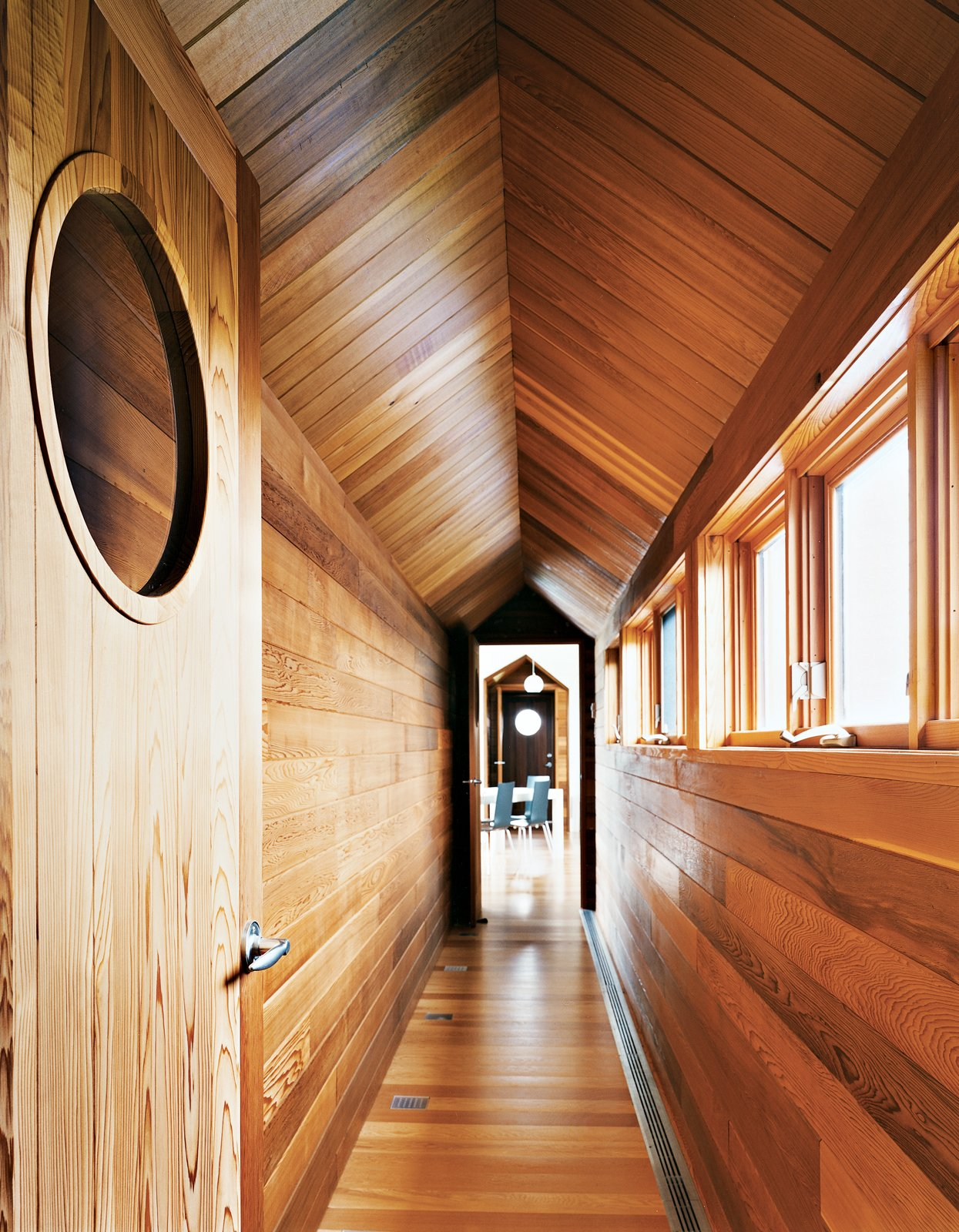 The view from the master bedroom down the long cedar corridor into the living room is one of the home's real pleasures. Tagged: Hallway and Medium Hardwood Floor.  Photo 7 of 12 in Material Spotlight: 11 Hardworking Uses of Western Red Cedar from Blue in the Facade