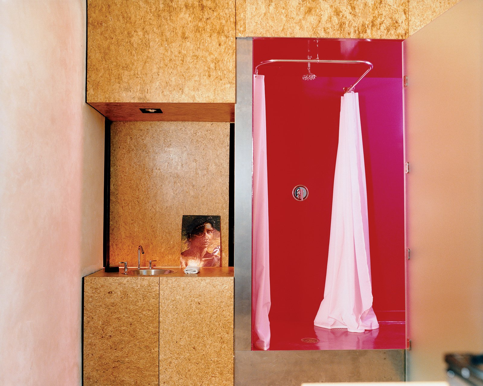 The Trzebiatowskis' bathroom retains the spirit of Arizona heat with its shocking magenta ceilings, floors, and walls. The vanity is anything but—opting for art instead of a mounted mirror—and is made from sanded and sealed oriented strand board (OSB), a waste material typically used in framing.  Photo 2 of 9 in 9 Unusual Modern Bathrooms from Xeros Effect