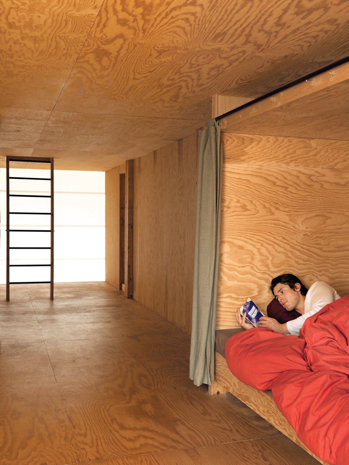 The second floor houses three lits bretons, boxlike compartments where the curtains can be drawn to close sleepers off from the world. Inside, each has a built-in shelf   for personal belongings and a favorite read. Tagged: Bedroom and Bed.  Photo 10 of 11 in Modern Wooden A-Frame Retreat in France