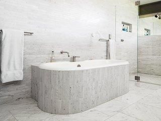 Mad About Marble: 20 Kitchens and Bathrooms - Photo 6 of 20 - In the master bathroom, Chris clad the tub and walls in Carrara marble. An AJ Wall sconce by Arne Jacobsen for Louis Poulsen sheds some light on bathtub reading.