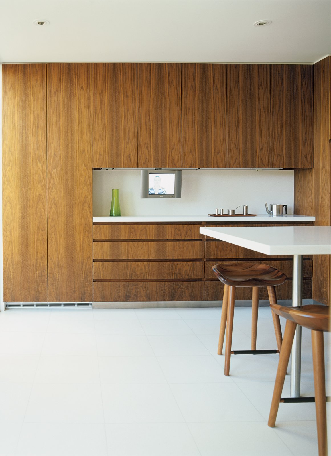 A 13-foot-long island in the kitchen, finished in the same white terrazzo as the floor, serves as an informal dining area. Bassam replicated the kitchen's walnut-veneered cabinetry in the study and master bedroom for continuity. Tagged: Kitchen, Engineered Quartz Counter, Porcelain Tile Floor, and Wood Cabinet.  Photo 4 of 6 in Pursuing Perfection