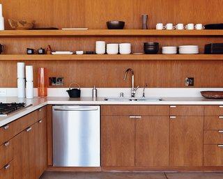 The kitchen cabinetry, custom designed by the architects, is smooth brown teak. The faucet is by Hansgrohe, and the dishwasher is by Bosch.