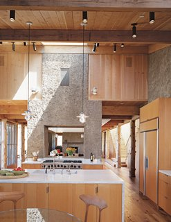"PISE Does It - Photo 2 of 4 - The house has the feel of a refined barn: The kitchen flows into the dining area, then into a den. The two PISE ""chimneys"" serve to demarcate the transitions and visually unite the space."