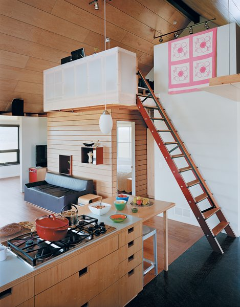 The kitchen cabinets with cutouts for handles were designed by a local woodworker. The stairs lead to a loft office where Joanna works, perched beside a quilt made by her great-grandmother.