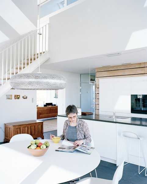 In one Danish family's green-home prototype, the kitchen receives tons of natural light thanks to triple-glazed, argon-filled windows and their super-insulated frames. Sophie sits at the Nava dining table in the kitchen, which is flanked by Gubi chairs and illuminated by the Aeros light by Ross Lovegrove for Louis Poulsen.