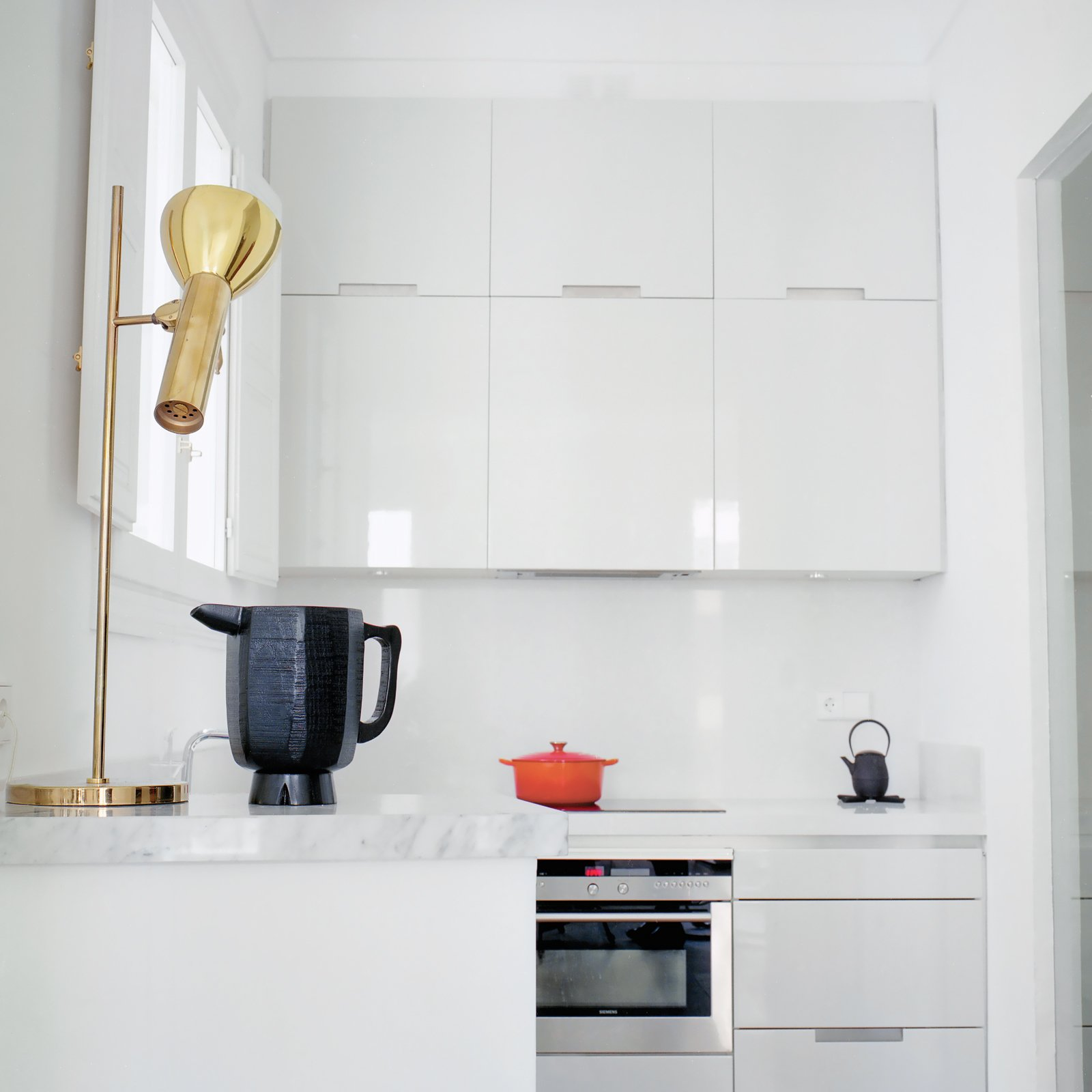 "Hayon and Klunder's kitchen is all white, down to the minimalist, lacquered Santos cabinets. When it comes to picking paint and fabric colors, Hayon advocates for grayed-out hues. ""My recommendation is that even when you use bolder colors make sure they have a percentage of gray in them,"" he says. ""If you use yellow, it should be yellow-gray. If a green is used it should be a green-gray."" Tagged: Kitchen, White Cabinet, Wall Oven, and Cooktops.  Best Photos from ""A Home Should Never Feel Like a Hotel Lobby"""