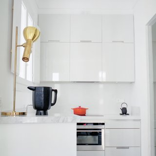 "Hayon and Klunder's kitchen is all white, down to the minimalist, lacquered Santos cabinets. When it comes to picking paint and fabric colors, Hayon advocates for grayed-out hues. ""My recommendation is that even when you use bolder colors, make sure they have a percentage of gray in them,"" he says. ""If you use yellow, it should be yellow-gray. If a green is used it should be a green-gray."""