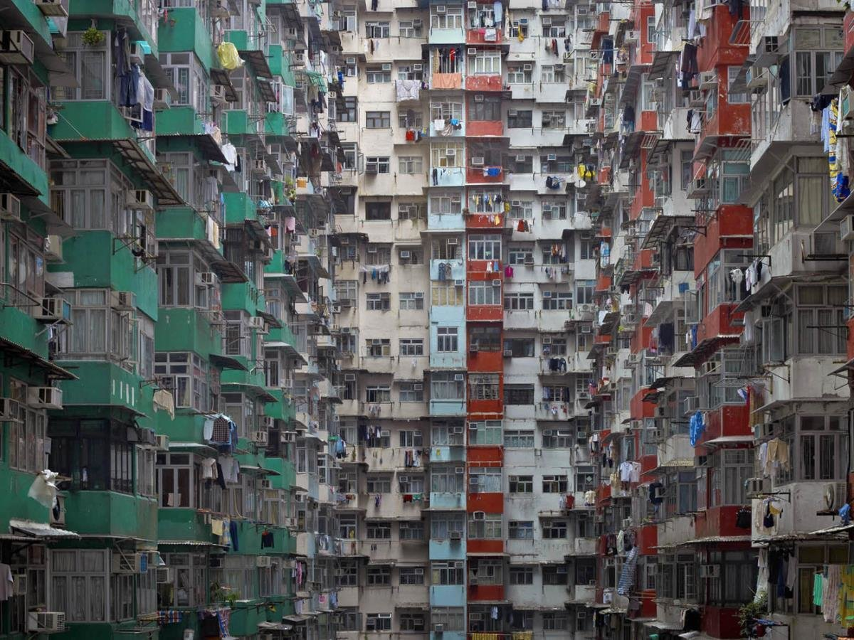 From a distance, the buildings resemble geometric patterns. However, close inspection reveals laundry, mops and other signs of domestic life. Photo by Michael Wolf, courtesy of the Flowers Gallery.  Photo 2 of 7 in Megacity Living in Hong Kong: Architecture of Density