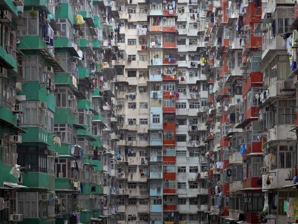 From a distance, the buildings resemble geometric patterns. However, close inspection reveals laundry, mops and other signs of domestic life. Photo by Michael Wolf, courtesy of the Flowers Gallery.