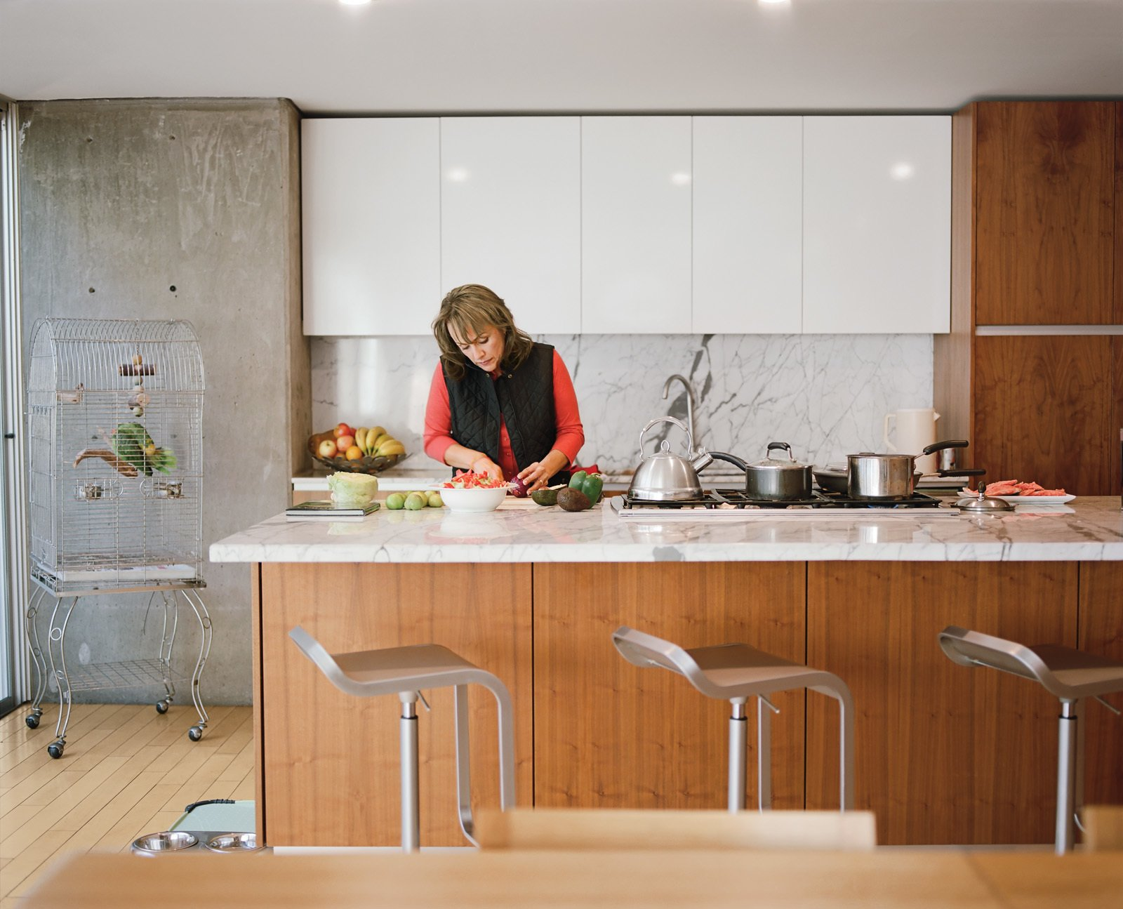 Angelica Becerril prepares food at the kitchen island; the Carrara marble countertop is one of the few luxury materials used in the house. Tagged: Kitchen, Marble Counter, and Wood Cabinet.  Photo 1 of 21 in Mad About Marble: 20 Kitchens and Bathrooms from Modern in Tijuana