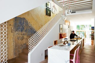 10 Modern Examples That Show How to Use Marble in the Kitchen - Photo 6 of 11 - In the kitchen, the continuous kitchen worktop and table are made of marble from Caledonia Marble. The pink Tamatik dining chairs are by Connie Chisholm and are from the Canadian design shop Made. The Blinding Love pendant lights are by Periphere, which has shops in Montreal and Toronto. The iron rails were inspired both by screens the couple had seen on their travels in the Middle East and by the ornate wrought ironwork favored by their Portuguese neighbors. Barzel Ironworks fabricated the banister to Sawatzky's design by slicing up iron pipe, welding it, and painting it.