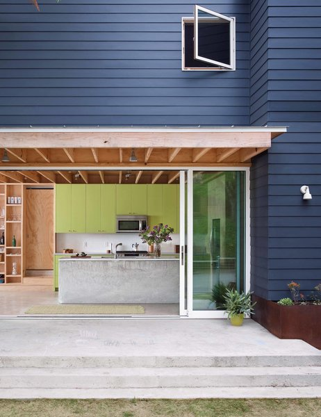 A tight construction budget informed the choices Sean Guess made as he designed a house for a couple in Austin, Texas. Budget-minded materials, like the James Hardie fiber-cement siding, helped hold construction costs to $130 per square foot. Sherwin-Williams's Cyberspace hue colors the exterior and Parakeet coats the custom kitchen cabinets by Austin Wood Works. The planter is made from Cor-Ten steel.