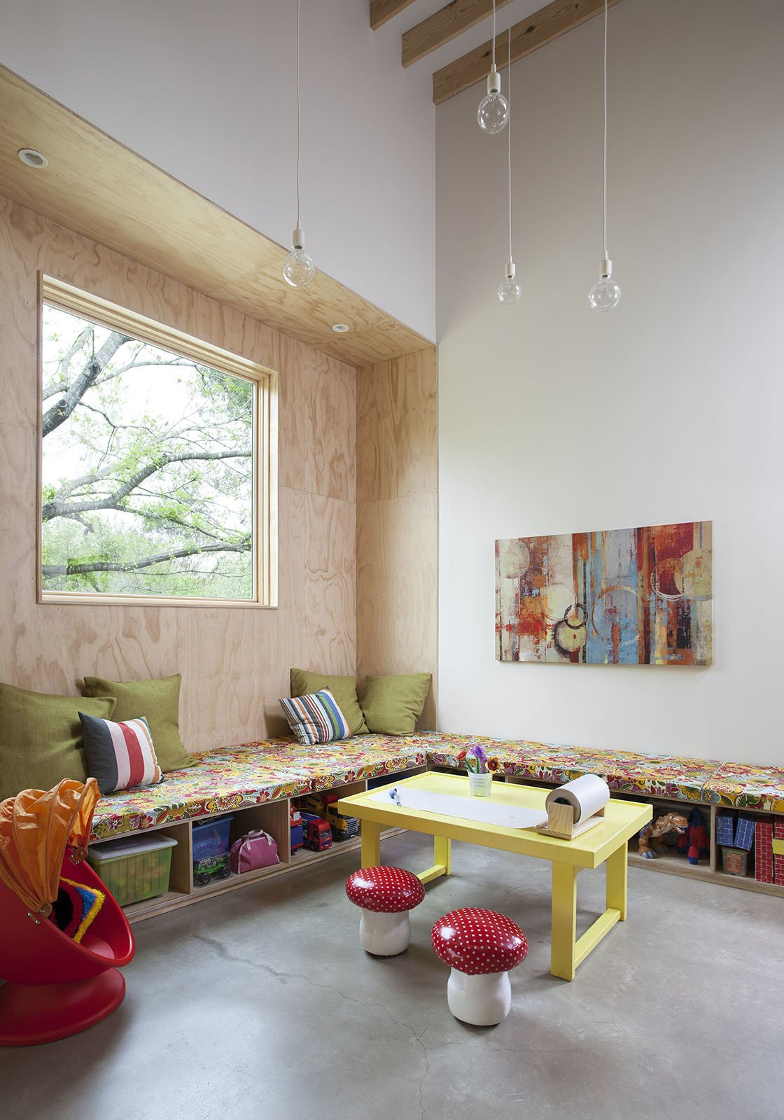 """In the playroom, built-in casework offers storage for toys. The yellow table was custom-built by the Kristin's father. The clear pendant lights are by Muuto. The """"toy zone"""" is adjacent to the kitchen so that Lowell and Kristin can prepare meals and keep an eye on their yound children, aged three and five. """"The residents wanted as little freestanding furniture as possible,"""" Guess says. 'We did a lot of benches, which are made out of plywood so they're fairly inexpensive.""""  127+ Inspiring Interior Ideas by Dwell from Inviting Kitchen Built on a Tight Budget"""