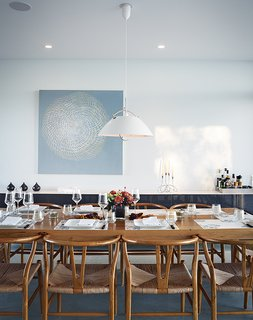 A pendant lamp by Hans Wegner for Carl Hansen & Søn hangs above a custom dining table by Cabinet. The paint is Cloud White by Benjamin Moore, and the painting, titled Meshed, is by Anna Yuschuk.