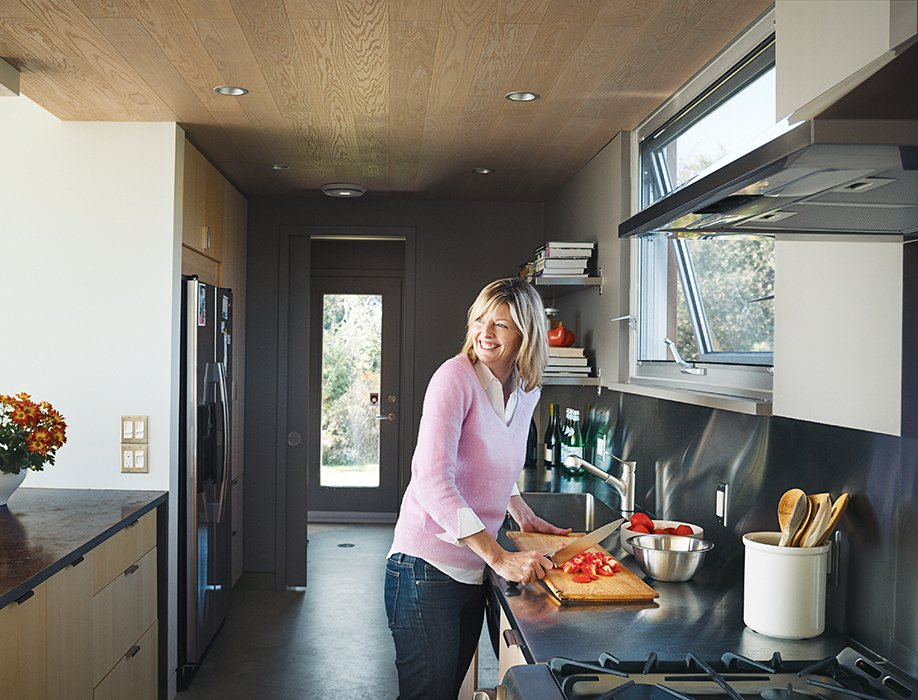 Crittenden Frum prepares food in the galley-style kitchen, which is outfitted with a Cascade Taupe Vintage countertop from Marble Trend.  Photo 5 of 11 in Modern Lakeside Retreat Stripped Down to the Basics