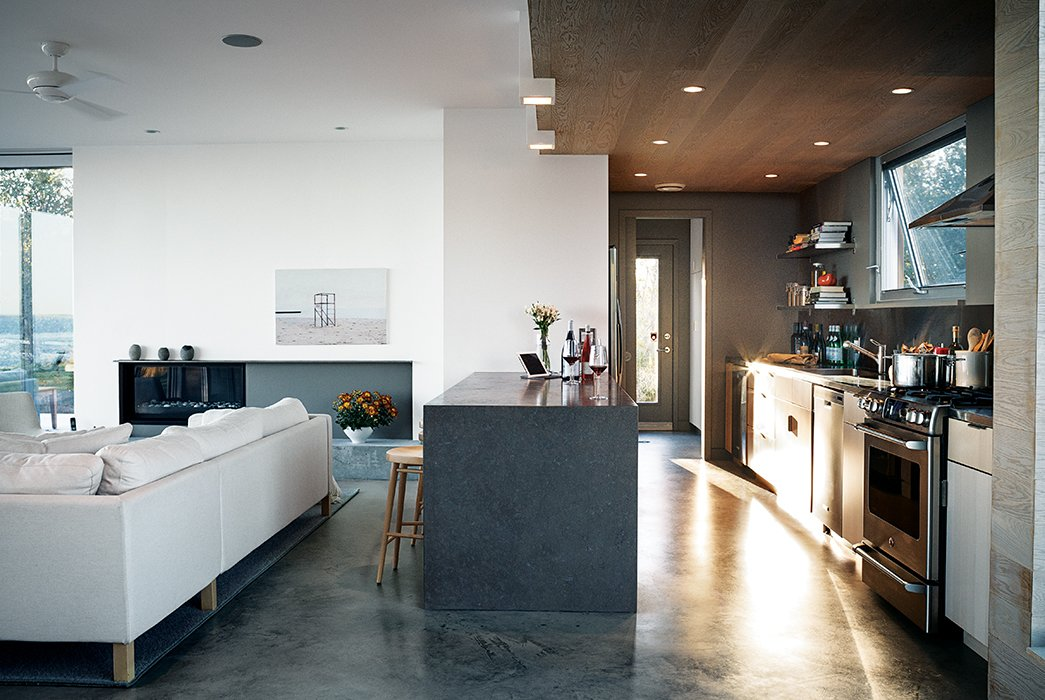 The cabinets are from Ikea, the range is by GE, and the Jenn-Air refrigerator is tucked unobtrusively into the pantry wall. The troweled concrete floor was poured in place by the builder, Peter Knudsen.