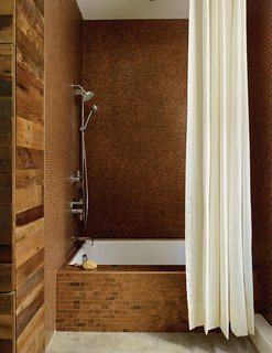 Bathroom Design Idea: Copper Color Scheme - Photo 2 of 2 - The walls are clad with metal penny tile in the Antique Copper finish from Design and Direct Source of Portland, Oregon. Linear-format tiles in the same finish line the tub.