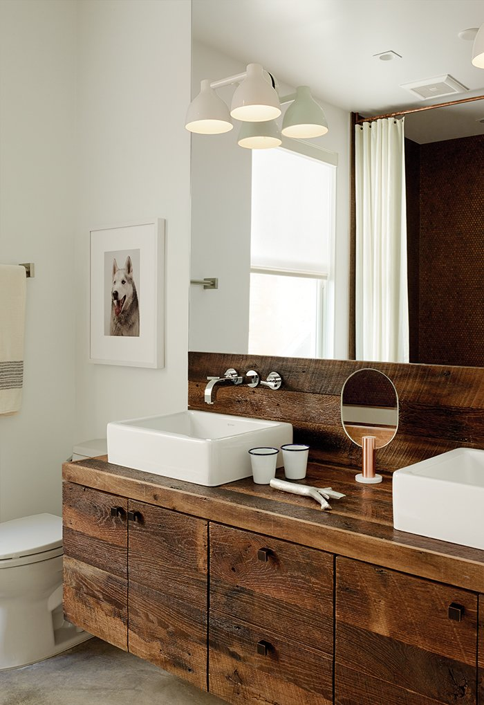 Builder Luke Gilligan of Gilligan Development used reclaimed oak planks from a deconstructed barn to create the bathroom's millwork. To achieve the rugged look, he sanded and wire-brushed the wood, then applied a clear stain. The sinks are from Duravit's Vero line and the cabinet pulls are from Top Knobs. Tagged: Bath Room, Wood Counter, Ceramic Tile Floor, and Vessel Sink.  Photo 1 of 2 in Bathroom Design Idea: Copper Color Scheme