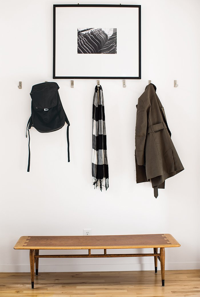 Inside the front door, coats hang from aluminum Bjärnum hooks by Ikea above a vintage Lane coffee table, which Magill bought from a coworker, and beneath a photograph by Beth Mercer. Tagged: Hallway and Light Hardwood Floor.  Photo 3 of 12 in A Versatile House Fulfills All This Musician's Needs