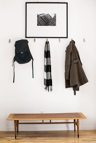 A Versatile House Fulfills All This Musician's Needs - Photo 2 of 11 - Inside the front door, coats hang from aluminum Bjärnum hooks by Ikea above a vintage Lane coffee table, which Magill bought from a coworker, and beneath a photograph by Beth Mercer.