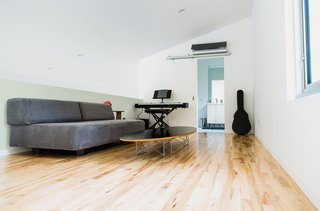 A Versatile House Fulfills All This Musician's Needs - Photo 4 of 11 - The loft is furnished with a Tillary sofa from West Elm and a wire-base Elliptical table by Charles and Ray Eames.