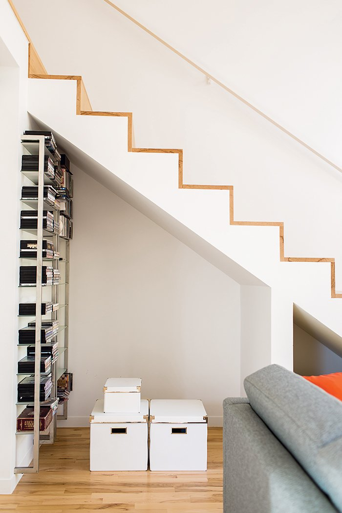 The staircase features a minimalist design with maple treads and edges. The alcove beneath the stairs allows Magill to stash things where they can still be easily accessed. The metal shelving system is another coworker castoff.  Photo 6 of 12 in A Versatile House Fulfills All This Musician's Needs