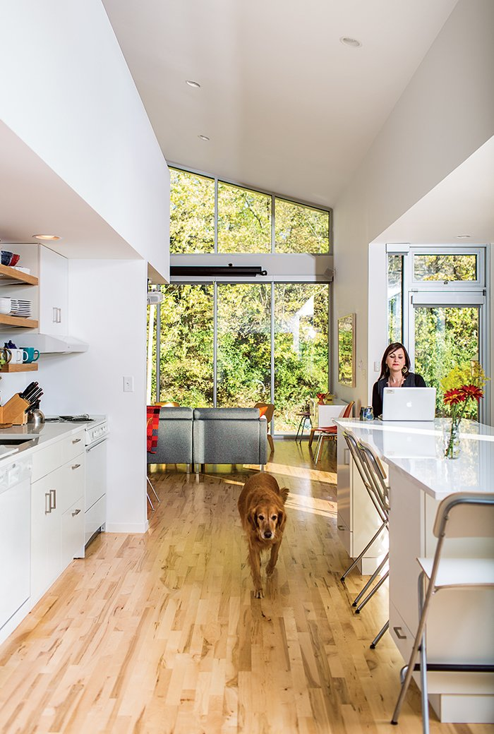 Sarah Magill and Copa, her golden retriever, relax in the kitchen of her home in Kansas City, where an eco-quartz-topped island can be used as a dining table—one of the home's many adaptable features. The Akurum cabinets and handles are from Ikea, as are the Franklin folding bar stools, and the appliances are compact models from Summit. Tagged: Kitchen, White Cabinet, and Light Hardwood Floor.  Photo 8 of 12 in A Versatile House Fulfills All This Musician's Needs