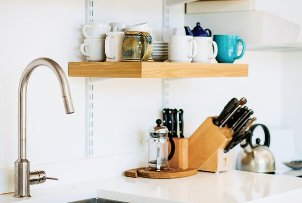 A Versatile House Fulfills All This Musician's Needs - Photo 8 of 11 - C & G Construction made the kitchen shelving from reclaimed cypress not used in the siding and decking. The White Cliff countertops are from Cambria, and the faucet is from Ikea.