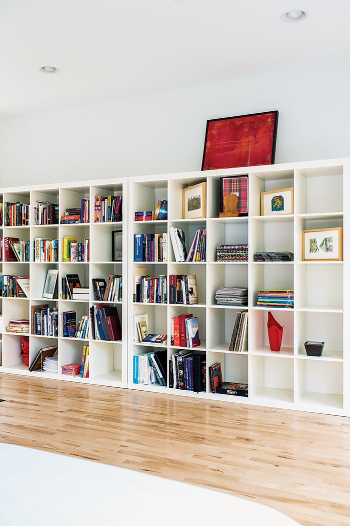 A pair of Ikea Expedit shelving units line one wall of the sleeping area.