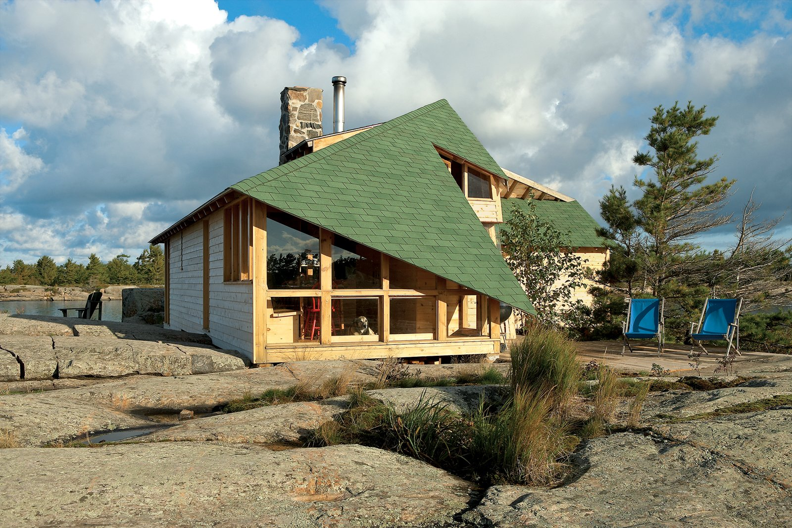 The winglike dips in the roofline situate and hold the house against the region's brutal winds. As the outdoor chairs attest, lifestyles here pass easily between inside and out; a long hike and a good swim are always just steps away Tagged: Exterior, Cabin Building Type, Shingles Roof Material, and Wood Siding Material.  Roofs by Aileen Kwun from On the Rock