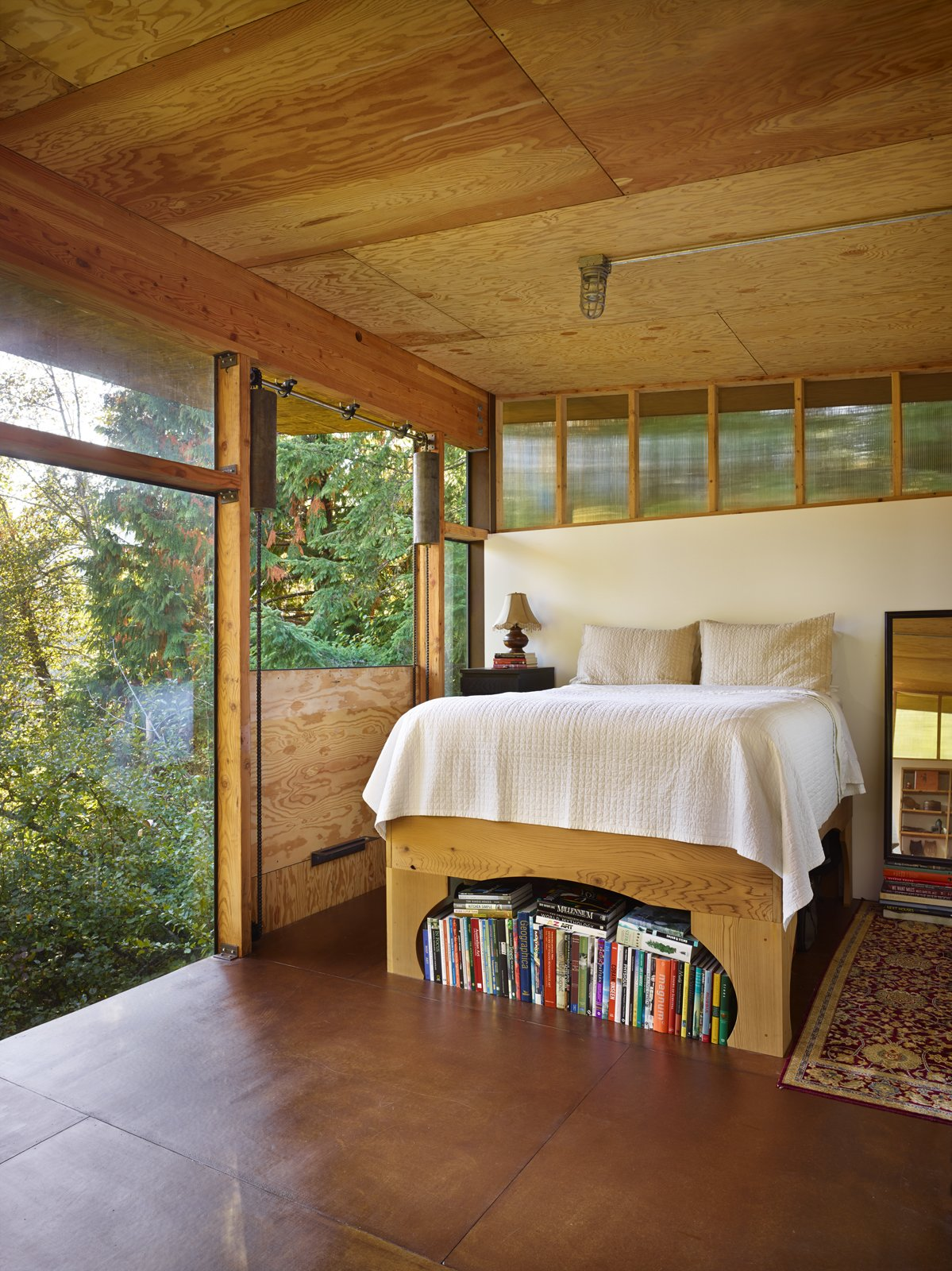 "A door next to the bed drops down, opening the room to its surroundings. ""It's a fantastic way to ventilate the space, but also makes sleeping in the loft feel like camping when it's down,"" Eerkes says.  Bedrooms by Dwell from An Eco-Friendly Compact Cabin in Washington"