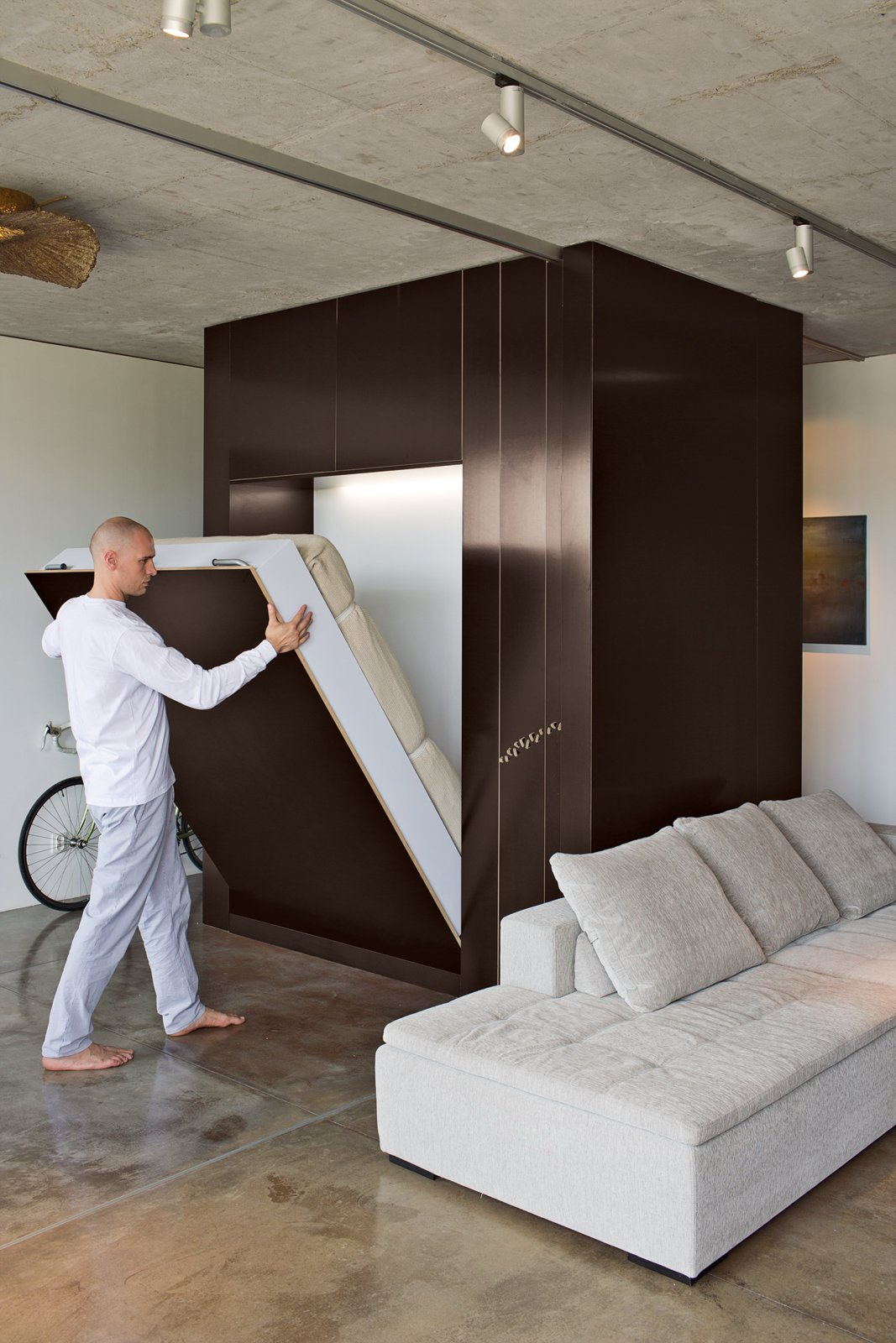 By lowering the custom Murphy bed and rolling a sliding plywood door, Novak-Zemplinski creates an insta-guestroom. Photo by Andreas Meichsner. Tagged: Bedroom and Bed.  Bedrooms by Dwell from Warsaw Loft with Multifunctional Furniture