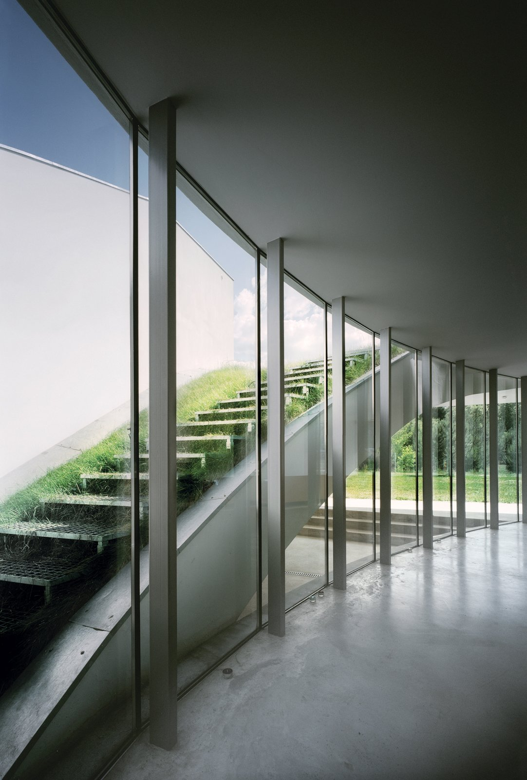 The expansive open-air living room on the first floor is framed with a curving wall of windows. The glass wall works as an outdoor atrium looking out on an exposed   sod-covered staircase and allows the room to be bathed in natural light.  190+ Best Modern Staircase Ideas by Dwell from Modernist Rural Getaway in Poland