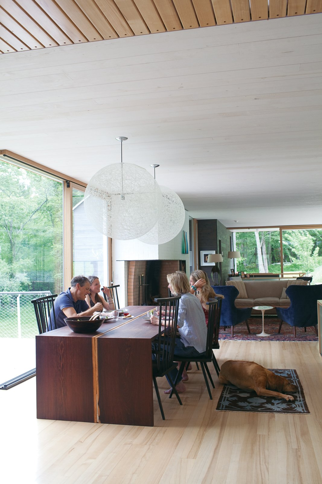The family relaxes in their home's dining   room, sited atop the old foundation. Organschi designed and fabricated the table of wenge wood; the chairs were inherited from his uncle; and the pendant lights are Bertjan   Pot designs for Moooi. Tagged: Light Hardwood Floor, Table, Pendant Lighting, and Dining Room.  Photo 1 of 9 in Gable-Roofed Rural Weekend Home in Connecticut