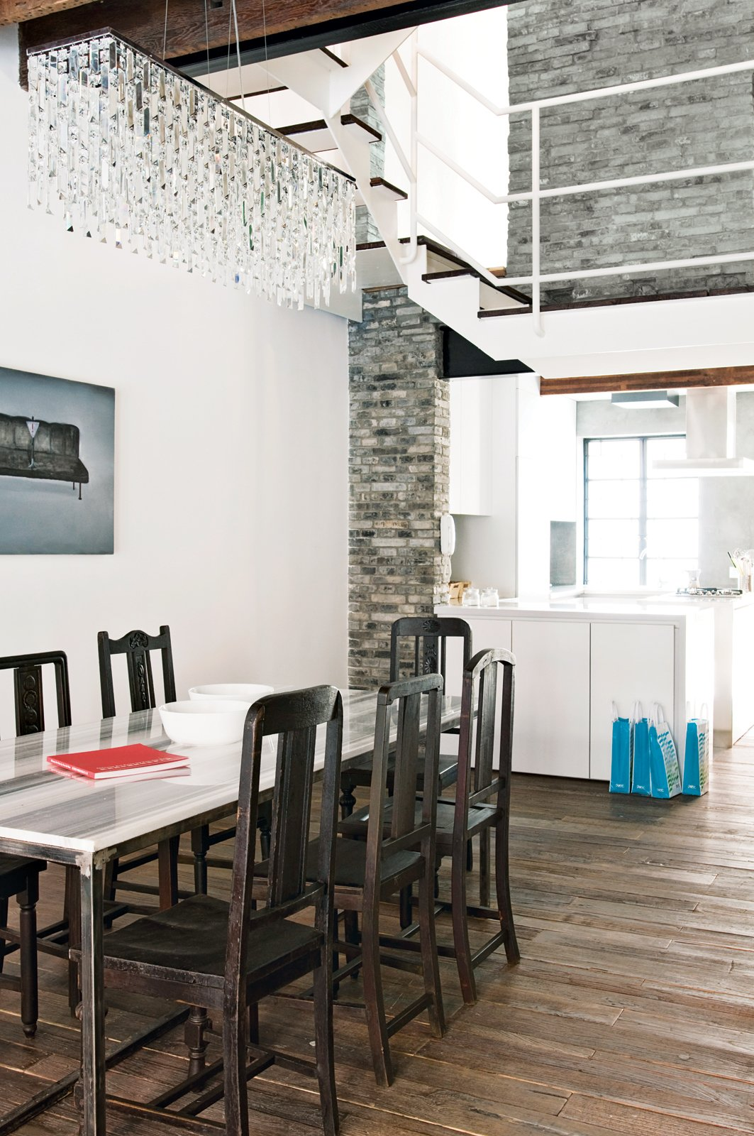 The dining room features vintage chairs.  The table and kitchen cabinets are custom pieces by Carbone; the chandelier came from a local shop. Tagged: Dining Room, Chair, Table, and Medium Hardwood Floor.  Photo 5 of 11 in Modern Lilong House Renovation in Shanghai