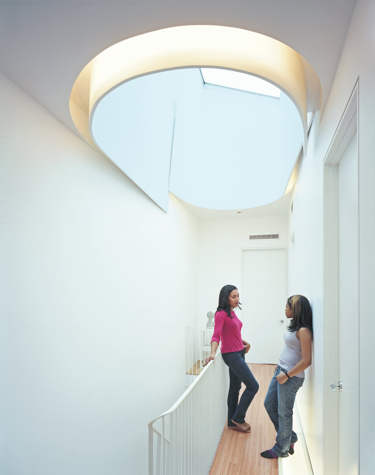 Keisha Martin and her cousin, Mickeda, chat underneath the house's crowning glory, the oculus, which allows light to spill onto each floor of the house. Tagged: Hallway and Medium Hardwood Floor.  Photo 1 of 7 in Modern Rowhouse Renovation in New York