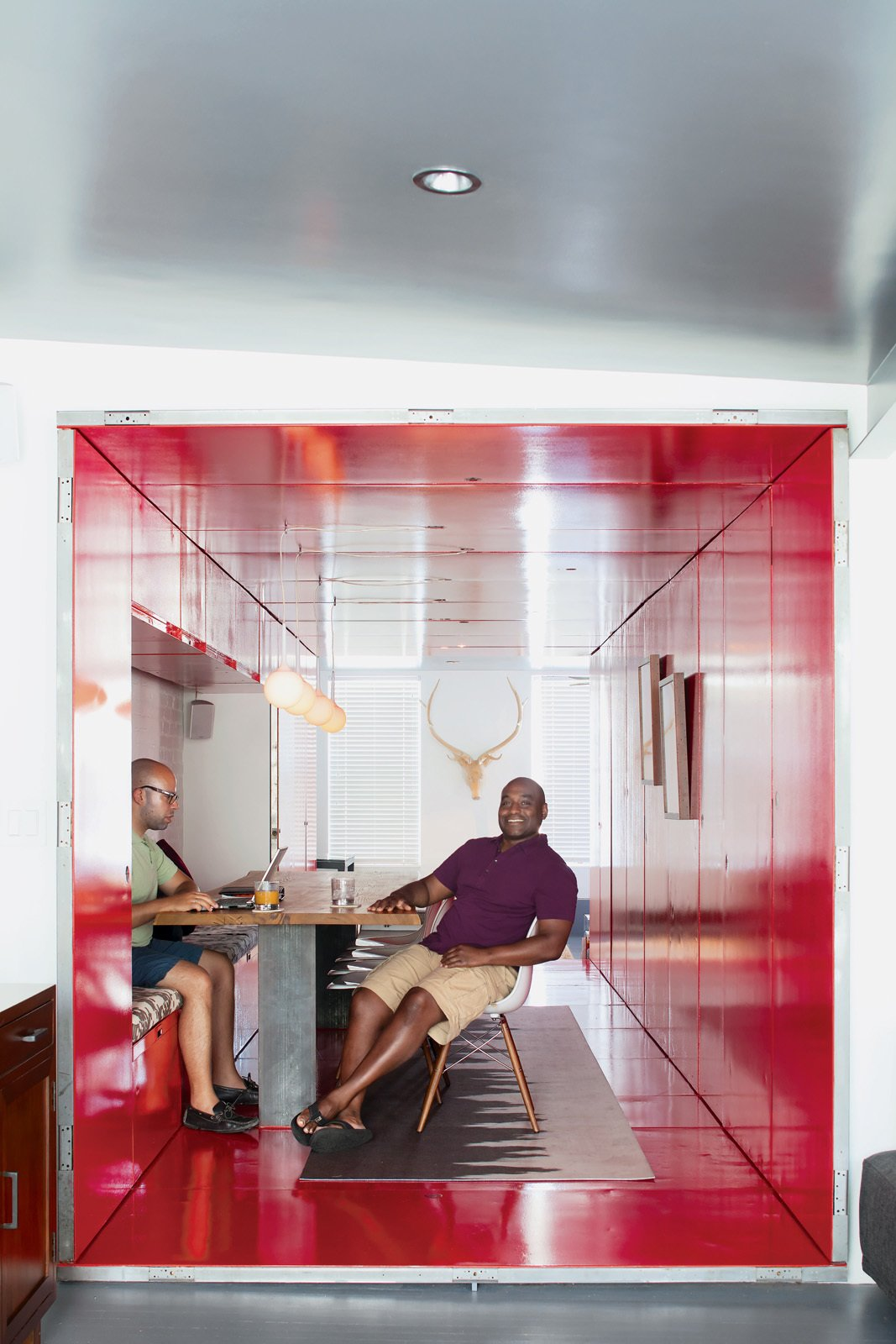 "By inserting a tunnel made from 36 reclaimed commercial doors and tearing down a handful of walls, LOT-EK and contractor Andreas Scholtz brought light into the formerly unused dark hallway in Maurice Russell (right) and Jorge Fontanez's apartment. The glossy Safety Red paint by Benjamin Moore catches the light by day but ""becomes a richer, darker, very relaxing red at night,"" Fontanez says.  Photo 1 of 10 in Tunnel Vision"