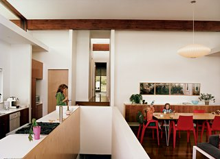 "Michele eats lunch in the kitchen; a view of the central hallway and master bedroom lays beyond. Three-year-old Maple slurps from a water bottle with Judith, five, at the dining table, also built by Jamie. The Arco armchairs are by Mario Bellino for Heller, and the Bubble lamp is by George Nelson for Herman Miller. The photograph series is by David Hilliard, titled ""That Glorious Society Called Solitude."""