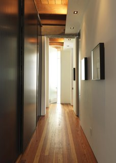 A long hallway from the living room separates the public and private sections of the home and extends the distance between the living quarters and work spaces.