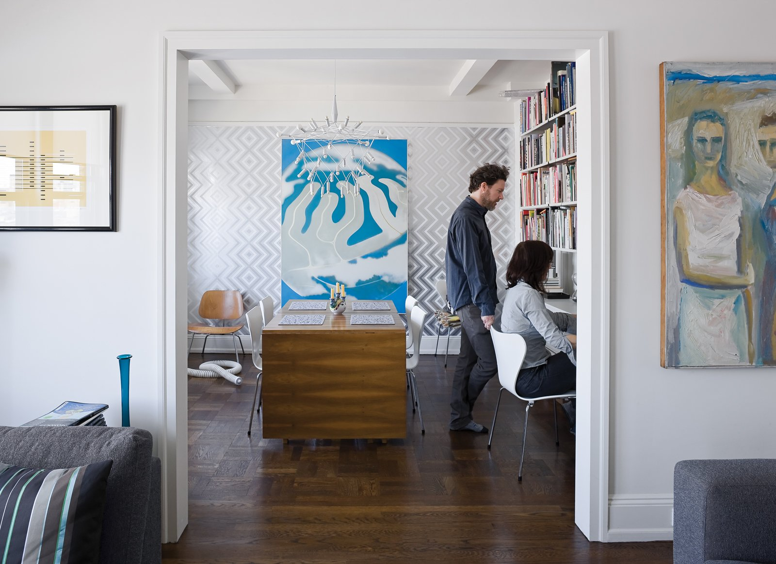 "A second bedroom was converted into a home office/dining room. A Dieter Rams 606 Universal Shelving System (below and opposite) lines the wall. The ""Ziggy Diamond"" wallpaper (behind the surreal Erle Loran painting) comes from Flavor Paper, a New Orleans firm that prints wall coverings to order, and the ingenious folding table is by Swedish designer Bruno Matthson. Tagged: Office and Chair.  Graphic Designers We Love by Aaron Britt from Creative Renovation in Brooklyn"