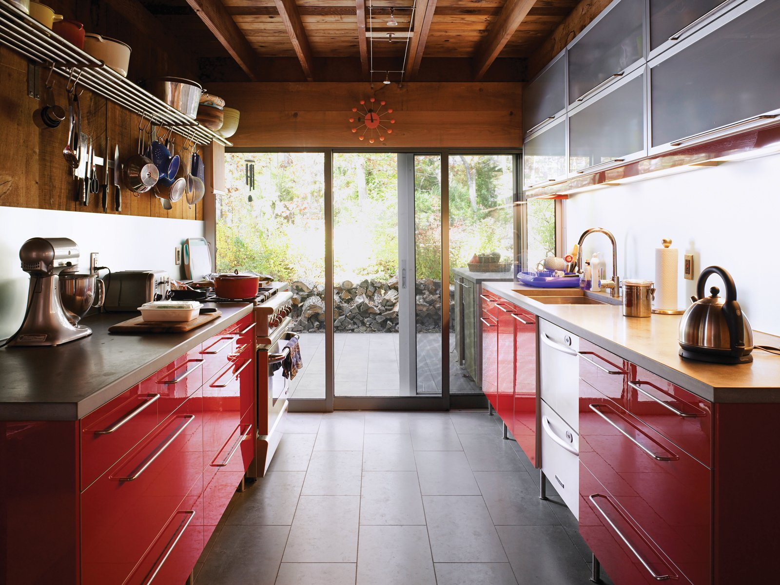 This sleek kitchen in the renovated Dolce and Burnham Residence hits warm notes with red lacquered cabinetry, cypress woodwork, and a leafy backyard vista. Tagged: Kitchen, Colorful Cabinet, Metal Counter, and Stone Slab Backsplashe.  Photo 6 of 17 in Long Island Summer Home Gets a Modern Addition