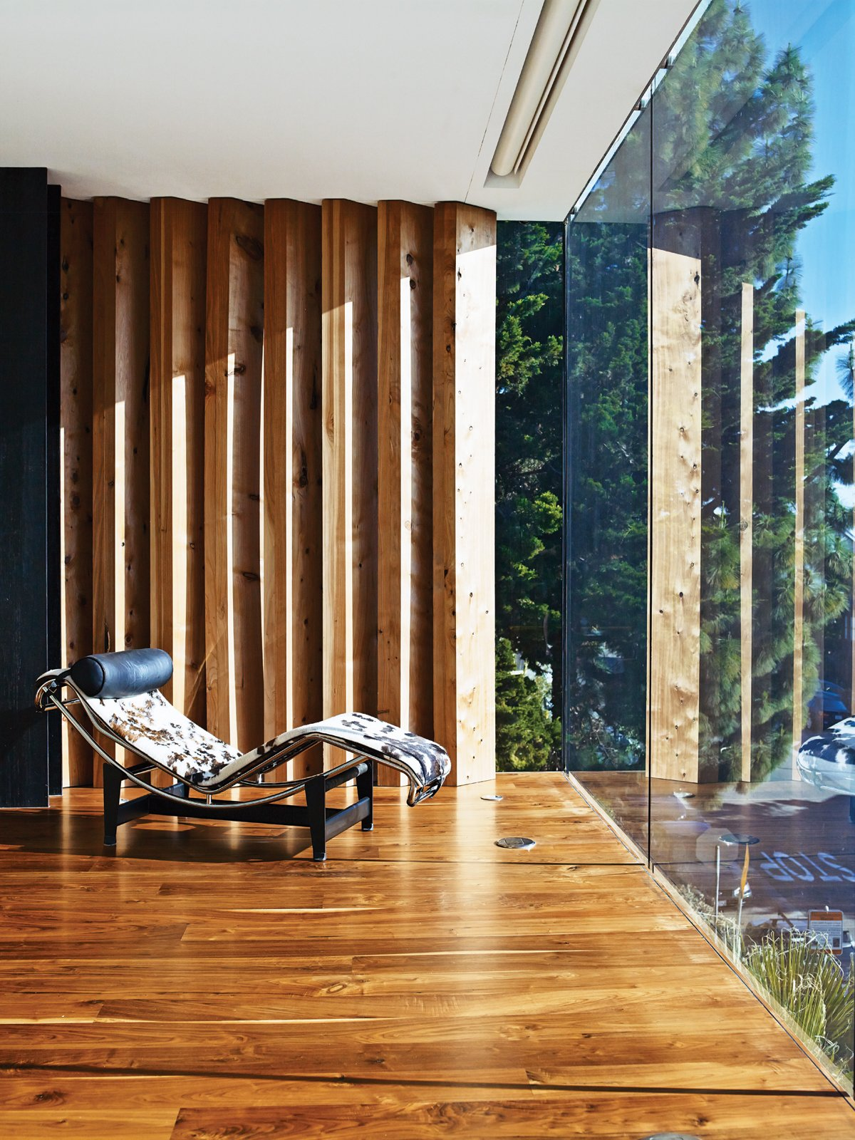 The master bedroom is defined on the north side by a series of indoor louvers, which allow the couple to frame and manage their views. Tagged: Living Room, Recliner, Medium Hardwood Floor, and Chair.  Photo 6 of 17 in Striking Slatted Wood and Glass Home in San Francisco