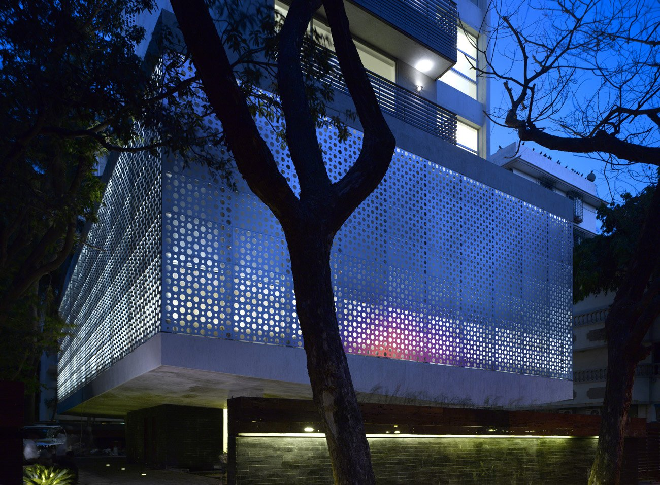 "The perforated aluminum cladding surrounds the lower-level public area, which contains the pools and gym for the tenants. Khanna and Schultz played with the idea of using stainless steel, but found that aluminum had the appropriate strength for the building's needs. ""With the lights glowing from inside, it turns the whole building into a big lantern at night,"" says Schultz.  Photo 2 of 17 in A Modern Aesthetic in Mumbai"