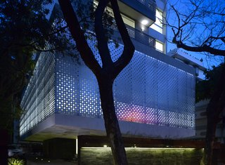"A Modern Aesthetic in Mumbai - Photo 2 of 17 - The perforated aluminum cladding surrounds the lower-level public area, which contains the pools and gym for the tenants. Khanna and Schultz played with the idea of using stainless steel, but found that aluminum had the appropriate strength for the building's needs. ""With the lights glowing from inside, it turns the whole building into a big lantern at night,"" says Schultz."