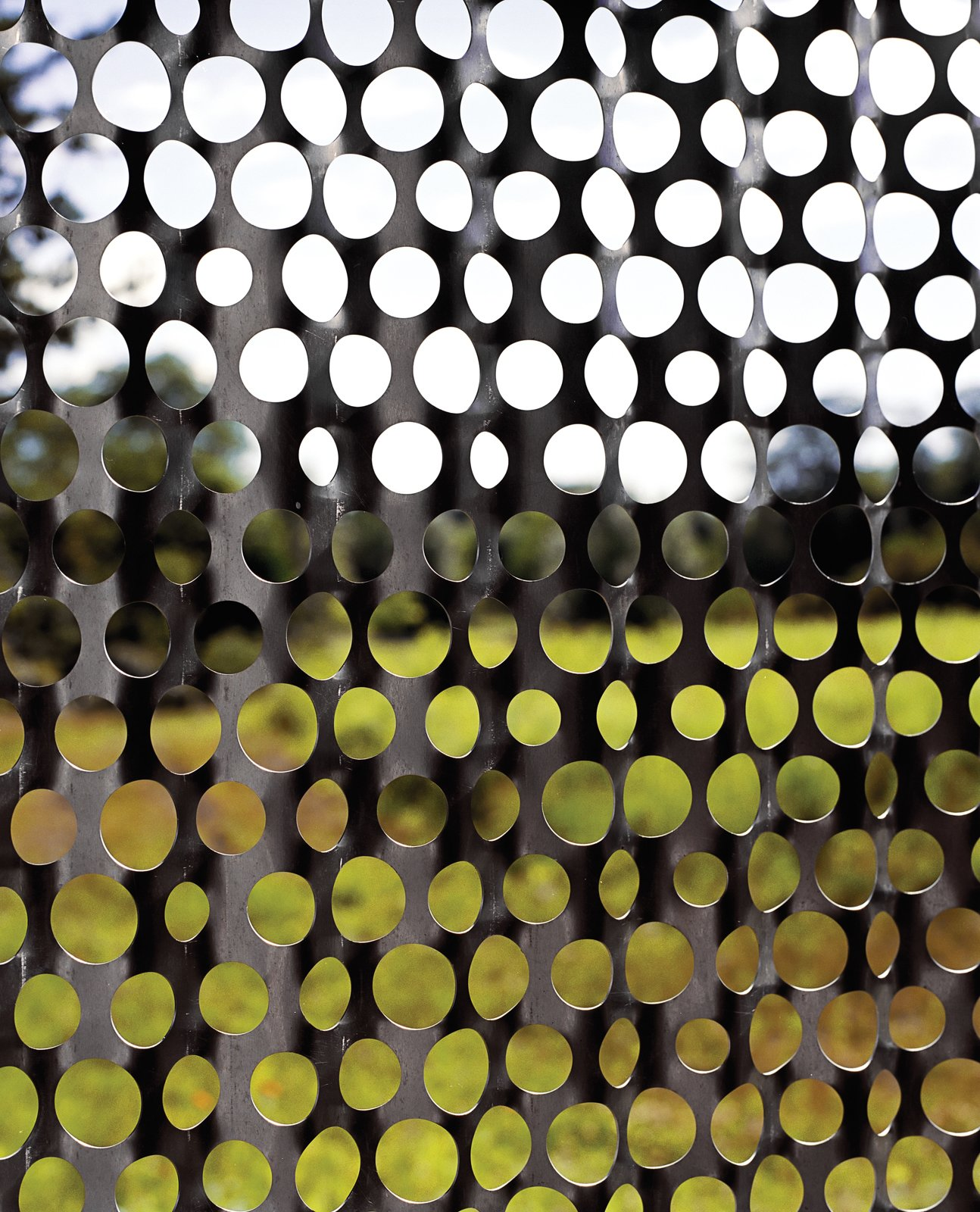 In the bathroom, perforated-metal screens create a pointillist perspective on the landscape.  New Grass Roots by Dwell from Uses of Perforated Metal