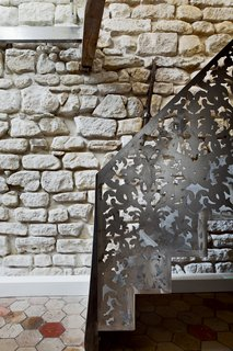 9 Unique Stair Railings - Photo 6 of 9 - In order to meld together a modern sensibility with the existing construction of an 18th century building in Paris, architect Michael Herrman used steel panels for the railings of the central stair in this apartment renovation. An abstract yet antique-inspired pattern was laser cut out of the steel to allow light to pass through.